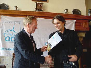 De redacteur overhandigt de nieuwe BODE aan de ODE-voorzitter