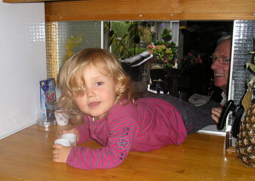 Louise zag speelgoed in de keuken en kroop door het doorgeefluik